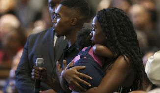 FILE - In this June 18, 2019 file photo Dravon Ames, holding microphone, speaks to Phoenix Police Chief Jeri Williams and Phoenix Mayor Kate Gallego, as his fiancee, Iesha Harper, right, holds 1-year-old daughter London, at a community meeting, in Phoenix. The Phoenix City Council will vote Wednesday, Aug. 26, 2020 on a settlement for the Black couple who had police officers point guns at them in front of their children last year after their young daughter took a doll from a store without their knowledge. (AP Photo/Ross D. Franklin, File)