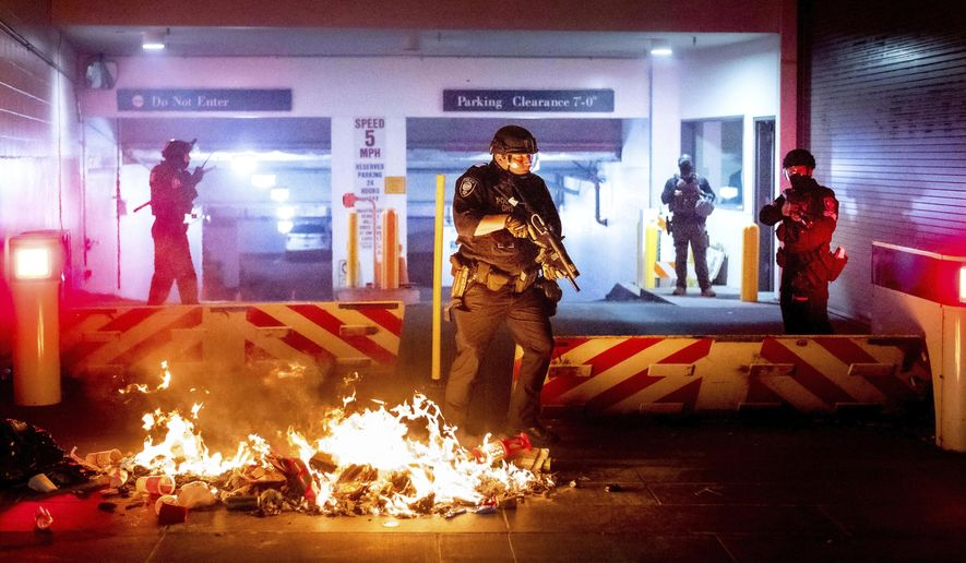 In this Aug. 2, 2020, file photo, a Department of Homeland Security officer emerges from the Mark O. Hatfield United States Courthouse after demonstrators lit a fire in Portland, Ore. (AP Photo/Noah Berger, File)