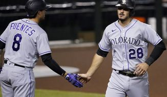 Colorado Rockies' Nolan Arenado (28) is greeted by Josh Fuentes (8) after scoring on a base hit by Matt Kemp during the first inning of a baseball game, Tuesday, Aug. 25, 2020, in Phoenix. (AP Photo/Matt York)