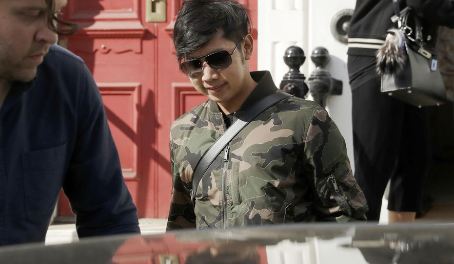 """FILE - In this April 5, 2017, file photo, Vorayuth """"Boss"""" Yoovidhya, whose grandfather co-founded the energy drink company Red Bull, walks to his car as he leaves a house in London. Thai judicial authorities said Wednesday that police will seek the arrest of Vorayuth on three charges, one more than had been announced a day earlier. (AP Photo/Matt Dunham, File)"""