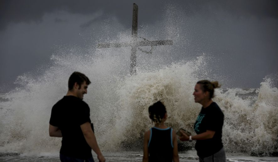 People talk as waves wash ashore and the outer bands of Hurricane Laura bring winds and rain Wednesday, Aug. 26, 2020, in High Island. ( Jon Shapley/Houston Chronicle via AP)
