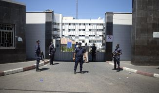 Hamas police officers guard the entrance of the Shifa Hospital after coronavirus cases were discovered in the hospital, in Gaza City, Wednesday, Aug. 26, 2020. Gaza health officials have reported the first death from COVID-19 since authorities detected the first local cases of the coronavirus earlier this week. (AP Photo/Khalil Hamra)
