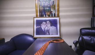 The tie belonging to the late evangelical Pastor Ovidio Valladares sits on a table in his former office, along with a portrait of him and his wife Aura Maria Valladares at Bethel evangelical church in Managua, Nicaragua, Wednesday, Aug. 12, 2020. Valladares died from COVID-19 related complications on June 9, and more than 40 evangelical leaders have died since March from the disease nationwide. (AP Photo/Alfredo Zuniga)
