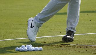 """Cameron Champ, wearing two different shoes Wednesday, Aug. 26, 2020, displays the message """"Jacob Blake BLM"""" during a practice round for the BMW Championship golf tournament at the Olympia Fields Country Club in Olympia Fields, Ill. (AP Photo/Charles Rex Arbogast)"""