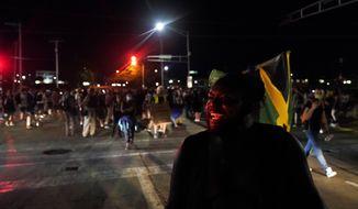 Oscar Walton speaks to fellow protesters while marching against the police shooting of Jacob Blake in Kenosha, Wis., Wednesday, Aug. 26, 2020. (AP Photo/David Goldman)
