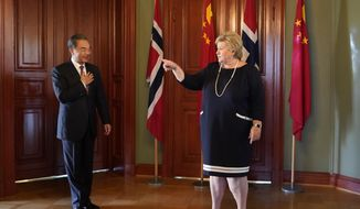 China's Foreign Minister Wang Yi, left, is welcomed by Norway Prime Minister Erna Solberg during a short courtesy visit to Norway, in Oslo, Thursday Aug. 27, 2020. The visit by Wang Yi and his delegation is part of a tour to several European countries. (Heiko Junge / NTB scanpix via AP)