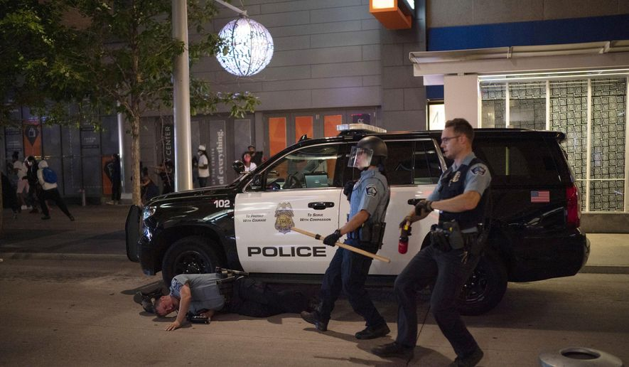 A Minneapolis police officer lies on the ground after being struck by an object Wednesday, Aug. 26, 2020, in Minneapolis. (Jeff Wheeler/Star Tribune via AP) ** FILE **