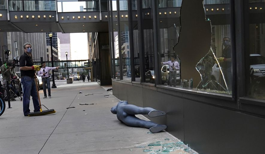 Tom Stellar, a pastor at Bethlehem Baptist Church, looks at broken windows while cleaning up damage outside Nordstrom Rack in Minneapolis on Thursday, Aug. 27, 2020.  An emergency curfew expired and downtown Minneapolis was calm Thursday morning after a night of unrest that broke out following what authorities said was misinformation about the suicide of a Black homicide suspect.  (David Joles/Star Tribune via AP)
