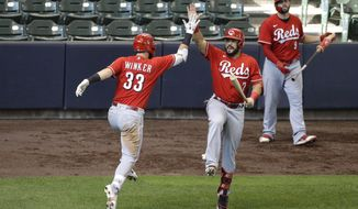 Cincinnati Reds' Jesse Winker (33) celebrates with teammate Eugenio Suarez (7) after hitting a solo home run during the third inning of the first baseball game of a doubleheader against the Milwaukee Brewers, Thursday, Aug. 27, 2020, in Milwaukee. (AP Photo/Aaron Gash)