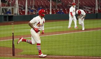 St. Louis Cardinals' Kolten Wong, left, tosses his bat after earning a bases loaded walk allowing Yadier Molina, right, to score the game-winning run during the ninth inning of a baseball game against the Kansas City Royals Wednesday, Aug. 26, 2020, in St. Louis. (AP Photo/Jeff Roberson)
