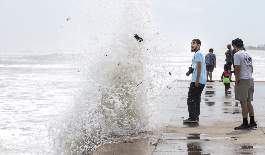 Jordan Razo steps back as a wave, stirred up by the approach of Hurricane Laura, crashes up and over the seawall Wednesday, Aug. 26, 2020 in Galveston, Texas. (Brett Coomer/Houston Chronicle via AP)