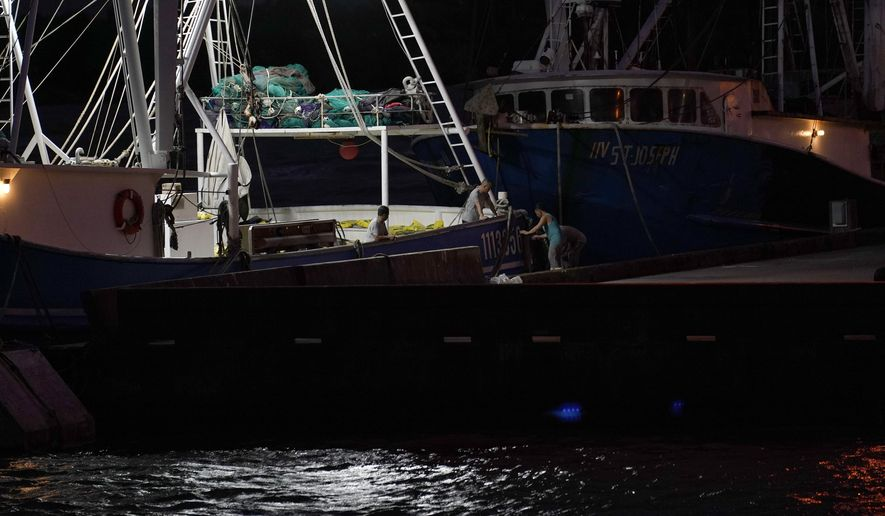 Crew members of a shrimp boat called the Sea Lion V prepare as they wait for Hurricane Laura to make landfall, Wednesday, Aug. 26, 2020, in Port Arthur, Texas. (AP Photo/Eric Gay)
