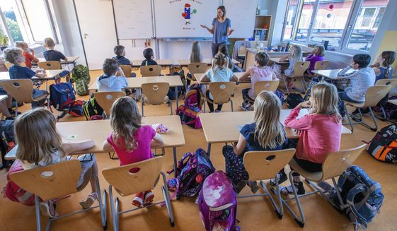 In this Monday, Aug. 3, 2020, file photo, teacher Francie Keller welcomes the pupils of class 3c of the Lankow primary school on their first school day after the summer holidays in Schwerin, Germany. Despite a spike in virus infections, European authorities are determined to send children back to school. (Jens Buettner/DPA via AP, file)