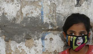 A Palestinian girl wear a face mask during a lockdown imposed following the discovery of coronavirus cases in the Gaza Strip, Thursday, Aug. 27, 2020. On Wednesday Gaza's Hamas rulers extended a full lockdown in the Palestinian enclave for three more days as coronavirus cases climbed after the detection this week of the first community transmissions of the virus in the densely populated, blockaded territory. (AP Photo/Hatem Moussa)