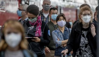 """In this file photo, passengers with face masks arrive in the main train station in Frankfurt, Germany, Thursday, Aug. 27, 2020. On Aug. 28, Democratic vice presidential nominee Sen. Kamala Harris said a national mask mandate that a President Joe Biden would put into effect would not be backed up by penalties. """"It's a standard. I mean, nobody's going to be punished,"""" Ms. Harris said on NBC's """"Today"""" show. (AP Photo/Michael Probst)"""