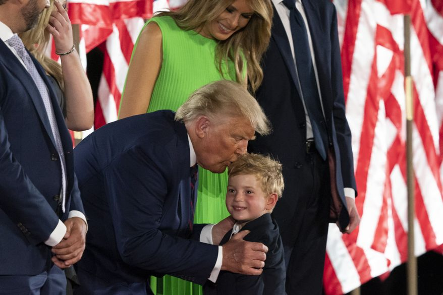 President Donald Trump kisses grandson Theodore James Kushner, with first lady Melania Trump, on the South Lawn of the White House on the fourth day of the Republican National Convention, Thursday, Aug. 27, 2020, in Washington. (AP Photo/Alex Brandon)