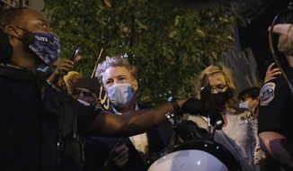 Sen. Rand Paul, R-Ky., center, and others, are escorted by Metropolitan Police after attending President Donald Trump's acceptance speech at the White House, Thursday night , Aug. 27, 2020, in Washington, after a crowd had enveloped Paul as he left the event and demanded that he acknowledge police shooting victim Breonna Taylor. (AP Photo/Yuki Iwamura)