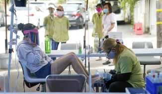 In this July 22, 2020, photo, Tyson Salomon, left, gets a pedicure outside Pampered Hands nail salon in Los Angeles. Gov. Gavin Newsom announced a new, color-coded process Friday, Aug. 28, 2020, for reopening California businesses amid the coronovirus pandemic that is more gradual than the state's current rules to guard against loosening restrictions too soon. Counties will move through the new, four-tier system based on their number of cases and percentage of positive tests. It will rely on those two metrics to determine a tier: case rates and the percentage of positive tests. (AP Photo/Ashley Landis) **FILE**