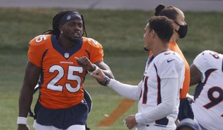 Denver Broncos running back Melvin Gordon, left, greets safety Justin Simmons as they take part in drills during an NFL football practice Friday, Aug. 28, 2020, in Englewood, Colo. (AP Photo/David Zalubowski)