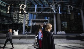 People walk past the closed Trump International Hotel Vancouver, in Vancouver, British Columbia, Friday, Aug. 28, 2020. (Darryl Dyck/The Canadian Press via AP)