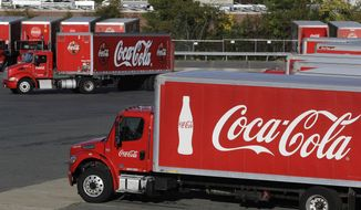FILE - In this Oct. 14, 2019 file photo a truck with the Coca-Cola logo, behind left, maneuvers in a parking lot at a bottling plant in Needham, Mass.  On Friday, Aug. 28, 2020, Coca-Cola is offering voluntary buyout packages to approximately 4,000 employees as it looks to limit the number of potential layoffs while streamlining its business.  (AP Photo/Steven Senne, File)