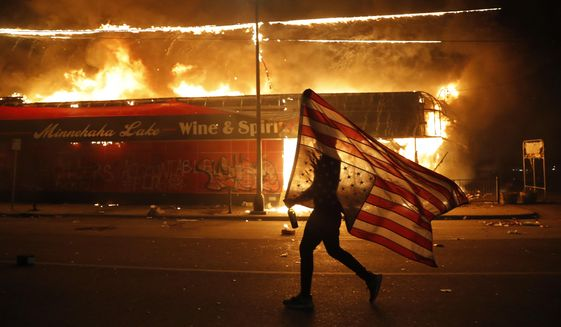 """A protester carries a U.S. flag upside down, a sign of distress, next to a burning building, Thursday, May 28, 2020, in Minneapolis during protests over the death of George Floyd. Speaking at the Republican National Convention, President Donald Trump said, """"The Republican Party condemns the rioting, looting, arson and violence we have seen in Democrat-run cities all, like Kenosha, Minneapolis, Portland, Chicago and New York, and many others."""" (AP Photo/Julio Cortez, File)"""