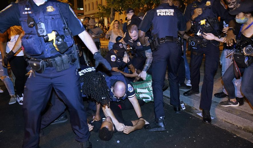 Metropolitan Police confront protesters on the ground along a section of 16th Street NW, renamed Black Lives Matter Plaza, Thursday night, Aug. 27, 2020, in Washington, after President Donald Trump had finished delivering his acceptance speech from the White House South Lawn. (AP Photo/Julio Cortez) **FILE**