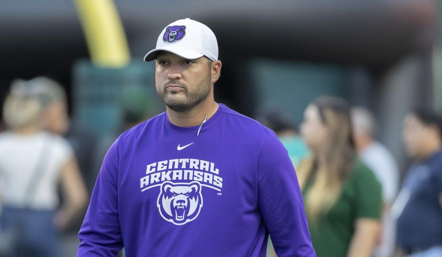 """FILE - In this Sept. 21, 2019, file photo, Central Arkansas head coach Nathan Brown walks on to the field before the start of an NCAA college football game against Hawaii in Honolulu. When Central Arkansas and Austin Peay signed up to play in the first game of the college football season, little did they know how notable it would become. The FCS schools will kick off the shortened season Saturday, Aug. 29, 2020, in the Guardian Classic before a limited number of fans amid the COVID-19 pandemic. Brown says """"we are the show in Week Zero and the game to really kick off football, not just college football but also professional football."""" (AP Photo/Eugene Tanner, File)"""