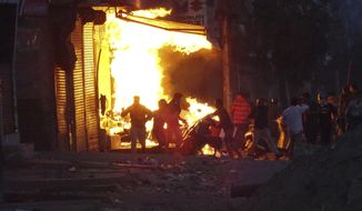 FILE - In this Tuesday, Feb. 25, 2020, file photo, a shop burns after it was set on fire by a mob in New Delhi, India. Indian police violated human rights during deadly religious riots in New Delhi earlier this year, Amnesty International said in a report released Friday, Aug. 28, 2020. It said police beat protesters, tortured detainees and in some cases took part in riots with Hindu mobs. Authorities say more than 50 people were killed when clashes broke out between Hindus and Muslims over a controversial citizenship law in February in the worst rioting in the Indian capital in decades. (AP Photo)