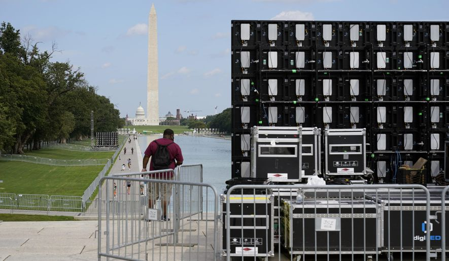 With the Washington Monument in the background, people walk by equipment being set up near the reflection pool on Thursday Aug. 27, 2020, in Washington, prior to the March on Washington, which is being held on Friday at the Lincoln Memorial. (AP Photo/Jacquelyn Martin)
