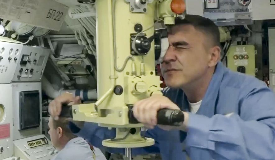 In this undated video grab provided by Russian Defense Ministry Press Service, A Russian submariner looks in periscope during a naval exercise in the Bering Sea. The Russian navy has conducted massive war games near Alaska involving dozens of ships and aircraft, the biggest such drills in the area since Soviet times. (Russian Defense Ministry Press Service via AP)
