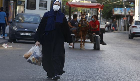 A Palestinian women wears a face mask carries her shopping during a lockdown imposed following the discovery of coronavirus cases in the Gaza Strip, Thursday, Aug. 27, 2020. On Wednesday Gaza's Hamas rulers extended a full lockdown in the Palestinian enclave for three more days as coronavirus cases climbed after the detection this week of the first community transmissions of the virus in the densely populated, blockaded territory. (AP Photo/Hatem Moussa)