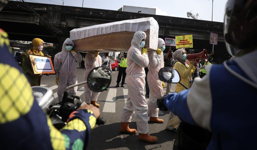 Government officials in protective suits carry a mock coffin as they walk around a busy intersection during a coronavirus awareness campaign to remind people of the risk of contracting COVID-19 and to always obey health protocols to curb the spread of the outbreak in Jakarta, Indonesia, Friday, Aug. 28, 2020. (AP Photo/Dita Alangkara)