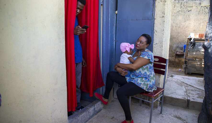 Verty chats on his phone while his wife Saint Jean holds up her 1-year-old daughter at their house in Port-au-Prince, Haiti, Tuesday, Aug. 25, 2020. The Trump administration has sharply increased its use of hotels to detain immigrant children before expelling them from the United States during the coronavirus pandemic. Verty says government contractors at a hotel where he was detained gave his family, including his daughter, cups of ice to eat to pass temperature checks prior to their deportation flight, even though they had tested negative for COVID-19. (AP Photo/Dieu Nalio Chery)