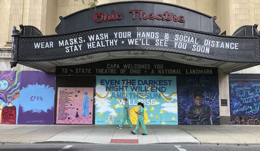 Workers in scrubs and masks walk past the Ohio Theatre in Columbus, Ohio, Wednesday, Aug. 26, 2020, amid the coronavirus pandemic. (AP Photo/Julie Carr Smyth)