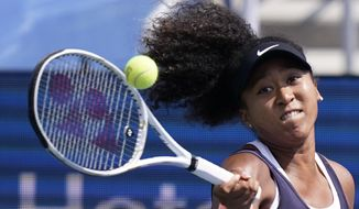 Naomi Osaka, of Japan, returns a shot from Elise Mertens, of Belgium, during the semifinals at the Western & Southern Open tennis tournament Friday, Aug. 28, 2020, in New York. (AP Photo/Frank Franklin II)