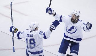 Tampa Bay Lightning left wing Ondrej Palat (18) celebrates his second goal of the game with teammate right wing Nikita Kucherov (86) during the second period of an NHL hockey Stanley Cup playoff game against the Boston Bruins in Toronto, Saturday, Aug. 29, 2020. (Cole Burston/The Canadian Press via AP)