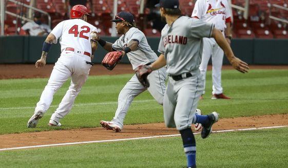 St. Louis Cardinals' Yadier Molina, left, is tagged out by Cleveland Indians first baseman Carlos Santana (41) during the 12th inning of a baseball game, Saturday, Aug. 29, 2020. (AP Photo/Scott Kane)