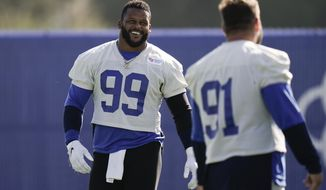 Los Angeles Rams defensive tackle Aaron Donald, left, shares a light moment with defensive tackle Greg Gaines during an NFL football camp practice Thursday, Aug. 27, 2020, in Thousand Oaks, Calif. (AP Photo/Jae C. Hong)