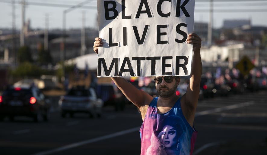 A Black Lives Matter supporter holds a sign as supporters of President Donald Trump attend a rally and car parade Saturday, Aug. 20, 2020, from Clackamas to Portland, Ore. (AP Photo/Paula Bronstein)