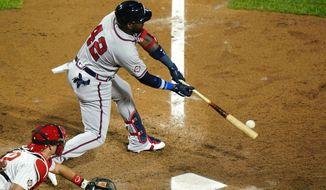 Atlanta Braves' Marcell Ozuna hits an RBI-single off Philadelphia Phillies pitcher Blake Parker during the fifth inning of a baseball game, Sunday, Aug. 30, 2020, in Philadelphia. (AP Photo/Matt Slocum)