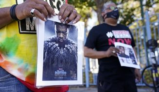 """A portrait of the late actor Chadwick Boseman as the character T'Challa in the 2018 film """"Black Panther"""" is held by a participant in a news conference celebrating his life, Saturday, Aug. 29. 2020, in Los Angeles. Boseman died Friday at 43 after a four-year fight with colon cancer. (AP Photo/Chris Pizzello)"""