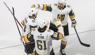 Vegas Golden Knights right wing Mark Stone (61) celebrates his goal against the Vancouver Canucks with teammates Shea Theodore, left, and Jonathan Marchessault (81) during the third period of Game 3 of an NHL hockey second-round playoff series, Saturday, Aug. 29, 2020, in Edmonton, Alberta. (Jason Franson/The Canadian Press via AP)