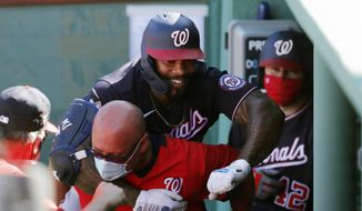 Washington Nationals' Eric Thames, top, celebrates his solo home run during the fifth inning of a baseball game against the Boston Red Sox, Sunday, Aug. 30, 2020, in Boston. (AP Photo/Michael Dwyer)