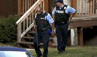 Members of the St. Louis Police Department work near the scene of a shooting Saturday, Aug. 29, 2020, in St. Louis. Two police officers have been shot and a suspect is believed to be barricaded in a house nearby according to the St. Louis Police Department. (David Carson/St. Louis Post-Dispatch via AP)