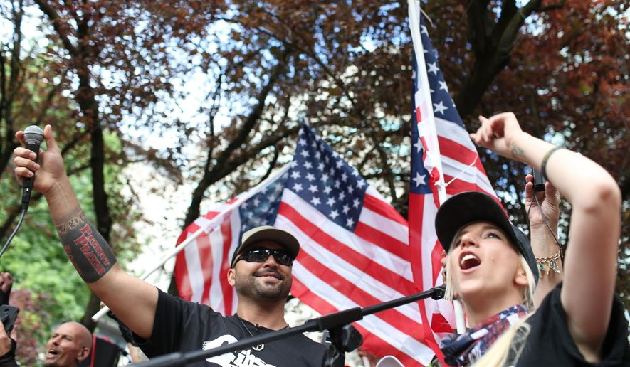 FILE - In this June 30, 2018, file photo, Joey Gibson, left, leader of Patriot Prayer, participates in the group's rally in Portland, Ore. The man who was fatally shot in Portland on Saturday, Aug. 29, 2020, as supporters of President Donald Trump skirmished with Black Lives Matter protesters was a supporter of a right-wing group called Patriot Prayer and a good friend of its founder, Gibson. (Mark Graves/The Oregonian via AP, File)