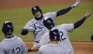 Tampa Bay Rays' Willy Adames, rear, celebrates with teammates after he hit a grand slam, also scoring Ji-Man Choi, Yandy Diaz and Yoshitomo Tsutsugo, during the fifth inning of a baseball game against the Miami Marlins, Sunday, Aug. 30, 2020, in Miami. (AP Photo/Wilfredo Lee)