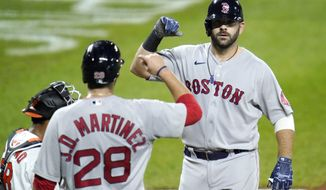 Boston Red Sox's Mitch Moreland, right, is greeted at home plate by J.D. Martinez (28) after hitting a three-run home run off Baltimore Orioles relief pitcher Miguel Castro during the ninth inning of a baseball game, Thursday, Aug. 20, 2020, in Baltimore. The Red Sox won 7-1. Martinez and Xander Bogaerts scored on the home run. (AP Photo/Julio Cortez)