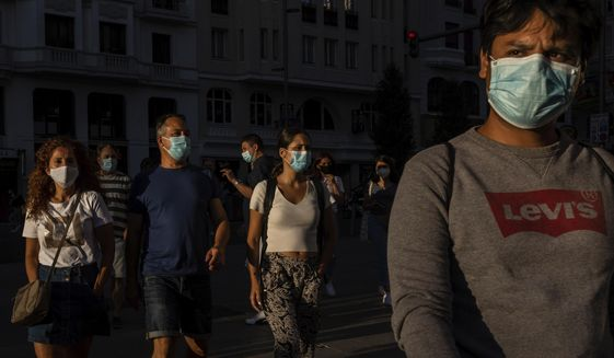 Pedestrians, wearing face masks protection to prevent the spread of the coronavirus, walk in Madrid, Spain, Saturday, Aug. 29, 2020. (AP Photo/Bernat Armangue)
