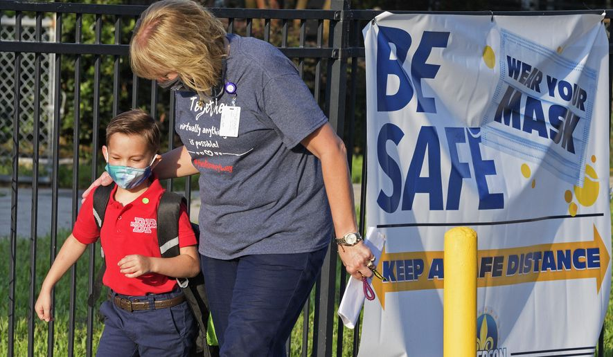 Teachers and staff welcome back students to Bissonet Plaza Elementary in the Jefferson Parish Public School District for in-person classes with coronavirus restrictions including temperature checks and masks in Metairie, La. Monday, Aug. 31, 2020. (Max Becherer/The Advocate via AP)